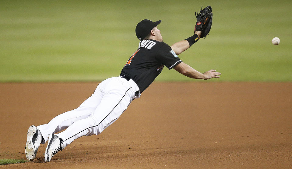 Miami Marlins first baseman J.T. Realmuto dives and misses the ball on a bunt pop-up by Washington Nationals' Trea Turner during the first inning of a baseball game Saturday, July 28, 2018, in Miami. (AP Photo/Brynn Anderson)