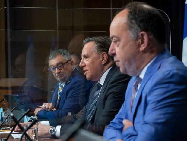 Quebec Premier François Legault, centre, speaks during a news conference Tuesday. Health Minister Christian Dubé, right, and public health director Dr. Horacio Arruda look on.  (Jacques Boissinot/The Canadian Press - image credit)