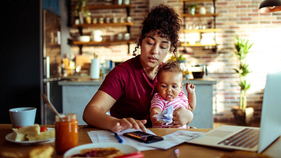 Close up of a mother using a phone with her daughter while having breakfast and doing bills.