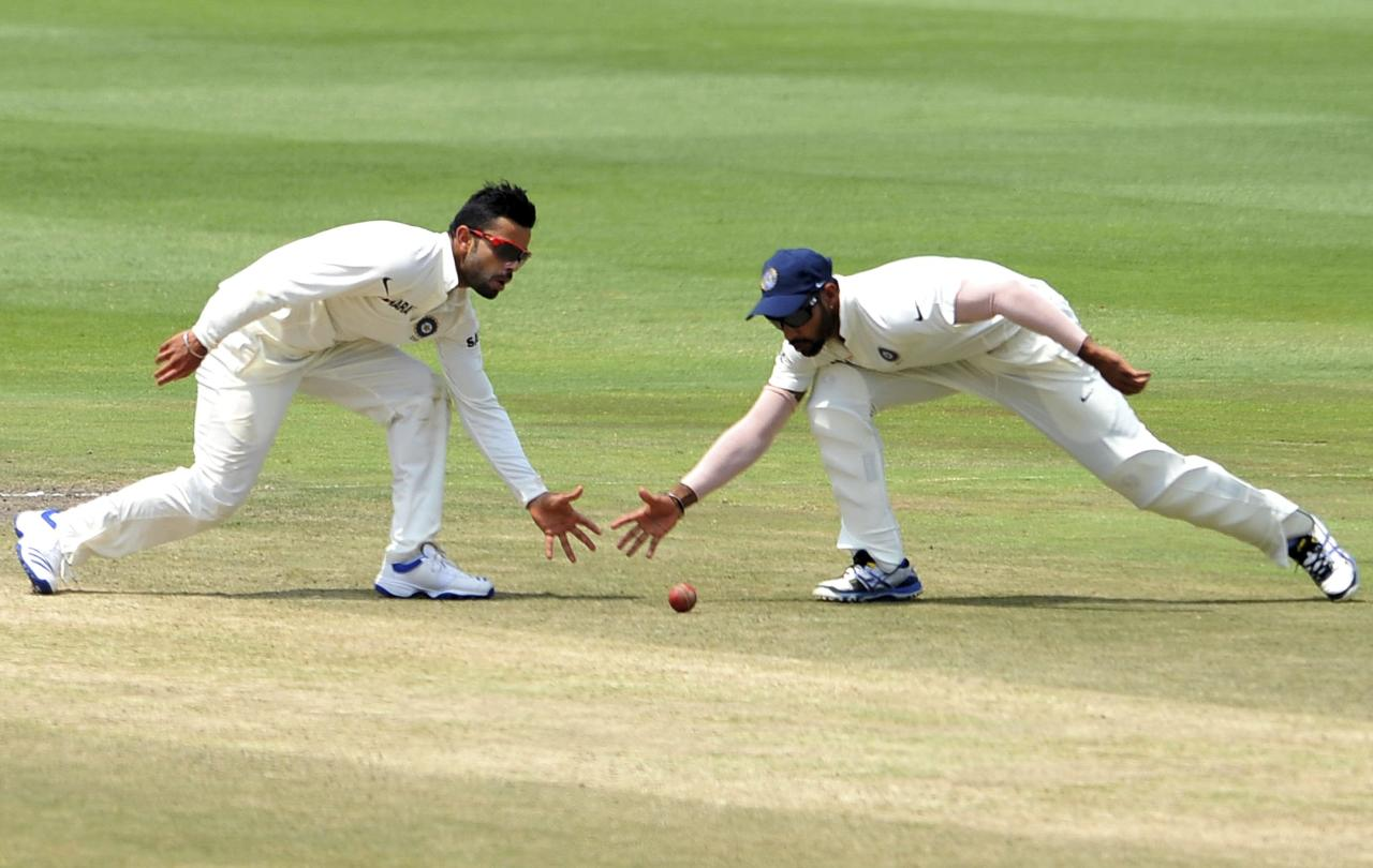 India's Virat Kohli (L) and Shikhar Dhawan field the ball during the final day of their test cricket match against South Africa in Johannesburg, December 22, 2013. REUTERS/Ihsaan Haffejee (SOUTH AFRICA - Tags: SPORT CRICKET TPX IMAGES OF THE DAY)