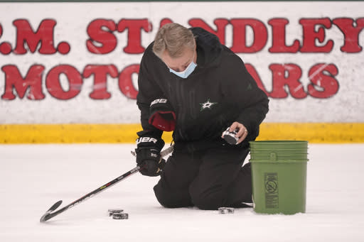 Dallas Stars head coach Rick Bowness picks up pucks between drills during NHL hockey training camp practice Wednesday, Jan. 6, 2021, in Frisco, Texas. (AP Photo/LM Otero)