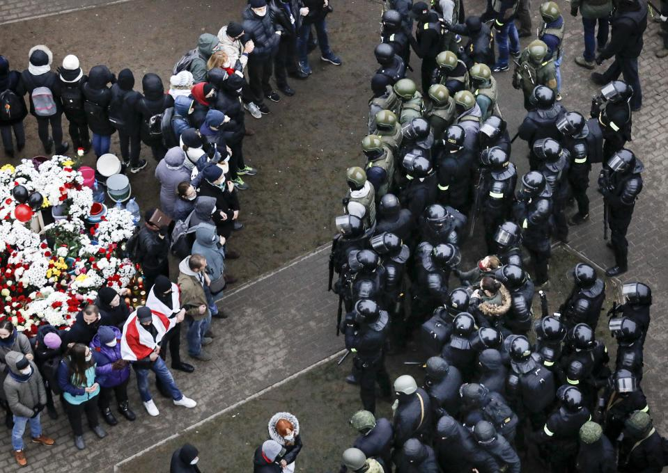 Belarusian riot police block demonstrators gather to honor 31-year-old Raman Bandarenka, who died Thursday at a Minsk hospital after several hours of surgery due to serious injuries, during an opposition rally to protest the official presidential election results in Minsk, Belarus, Sunday, Nov. 15, 2020. Protests have rocked Belarus since the August election that official results say gave Lukashenko a sixth term in office but that opponents and some polls workers claim were manipulated. (AP Photo)