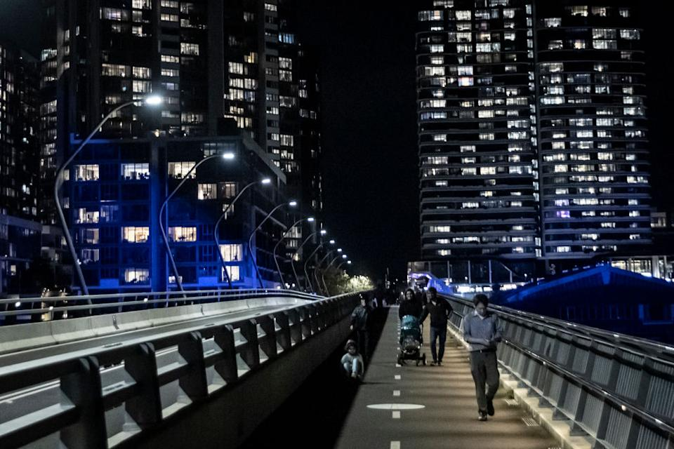 People walk along the Bennelong Bridge, which runs between Wentworth Point and Rhodes.