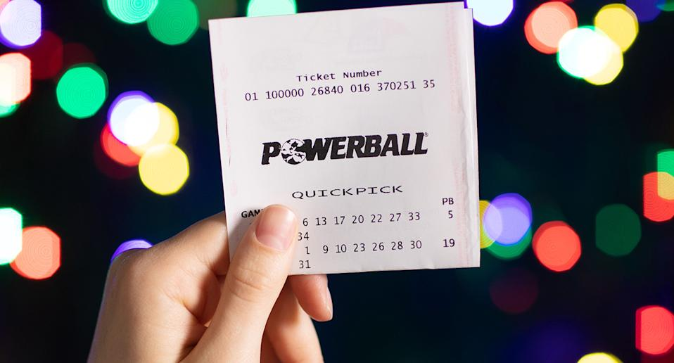 A Powerball ticket is held in the air.