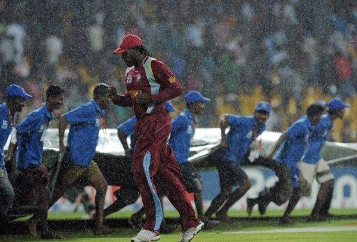 "West Indies batsman Chris Gayle (C) runs for cover as ground staff pull a tarp over the pitch during the World Twenty20 match on September 22. ""This was the only period available in the Future Tours Programme this year to conduct the tournament,"" an ICC spokesman told AFP"