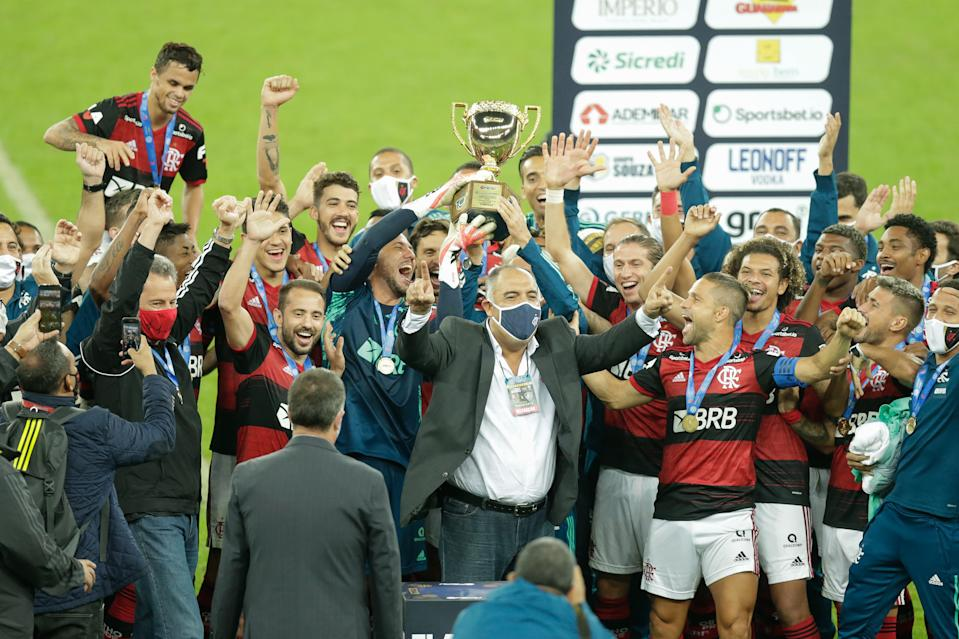 RIO DE JANEIRO, BRAZIL - JULY 15: Players of Flamengo lift the trophy after after winning a second leg match against Fluminense as part of the Campeonato Carioca Final at Maracana Stadium on July 15, 2020 in Rio de Janeiro, Brazil. The match is played behind closed doors and with precautionary measures against the spread of coronavirus (COVID-19). (Photo by Andre Coelho/Getty Images)