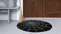 <p>Lure visitors with a spooky doormat.</p><p><strong>Step 1:</strong> Purchase an indoor/outdoor needle-punch carpet. To turn it into a circle: Mark the rug's center point with a white-colored pencil<em>.</em> Measure and mark the distance from that point to a spot about half an inch from the rug's edge. Cut a piece of string to that length. Tie one end of the string to the pencil and secure the other end of the string to the rug's center point with a tack. Pull the string taut and draw a large circle onto the rug; remove the string. Cut out the circle, just inside the white pencil mark, with sharp scissors.</p><p><strong>Step 2:</strong> Using a yardstick, evenly space and draw eight intersecting lines that cross the rug from edge to edge. Between those lines, draw arches around the mat, using our photo as a guide.</p><p><strong>Step 3:</strong> Lastly, coat the rug with a clear finishing spray, like Krylon Make It Last Clear Sealer<em>.</em> to protect your web from trick-or-treating feet. </p>