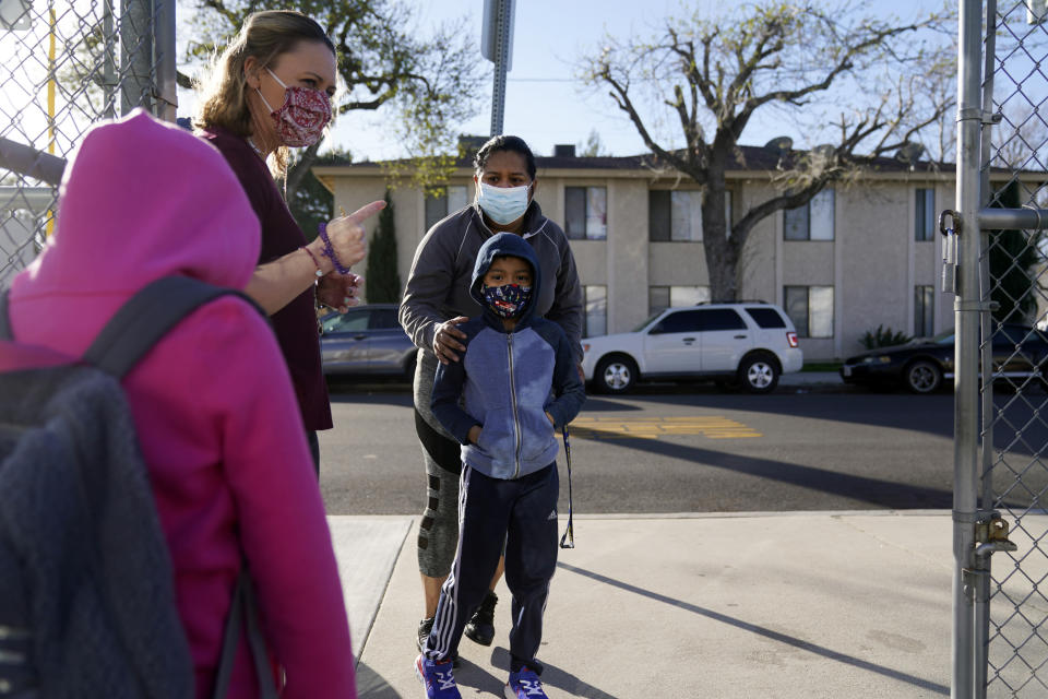 Assistant Principal Janette Van Gelderen, left, welcomes students at Newhall Elementary School Thursday, Feb. 25, 2021, in Santa Clarita, Calif. Elementary school students returned to school this week in the Newhall School District. (AP Photo/Marcio Jose Sanchez)