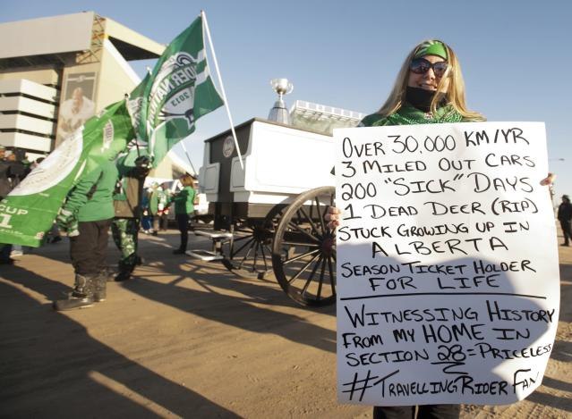 Connie Dobson holds up a sign during the Grey Cup parade on Tuesday, Nov. 26, 2013 in Regina, Saskatchewan. The Saskatchewan Roughriders defeated the Hamilton Tiger-Cats 45-23 in the 101st CFL Grey Cup on Sunday. (AP Photo/The Canadian Press, Liam Richards)