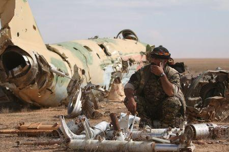 A Syrian Democratic Forces (SDF) fighter rests near destroyed airplane parts inside Tabqa military airport after taking control of it from Islamic State fighters, west of Raqqa city