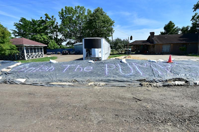 """A clear message to """"finish the pumps"""" is painted on tarp covering a levee protecting houses across from farmland flooded by backwaters in Holly Bluff. Wednesday, June 12, 2019."""