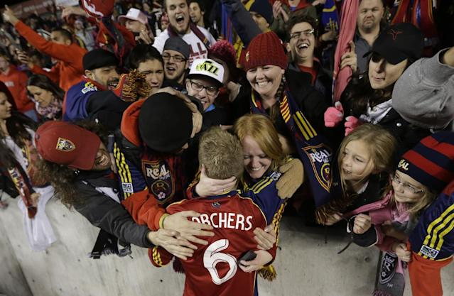 CORRECTS SCORE - Fans hug Real Salt Lake defender Nat Borchers (6) after Real Salt Lake defeated the Los Angeles Galaxy in the second leg of the MLS Western Conference semifinal Thursday, Nov. 7, 2013, in Sandy, Utah. Real Salt Lake won 2-0. (AP Photo/Rick Bowmer)