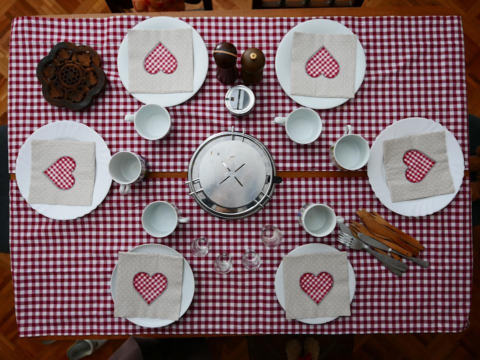 Party table set with tiled tablecloth and heart napkins for 6 guests on a special occasion (Photo: Daniel Thurler via Getty Images)