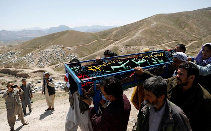 Men carry the coffin of one of the victims of yesterday's explosion during a mass burial ceremony in Kabul, Afghanistan May 9, 2021.