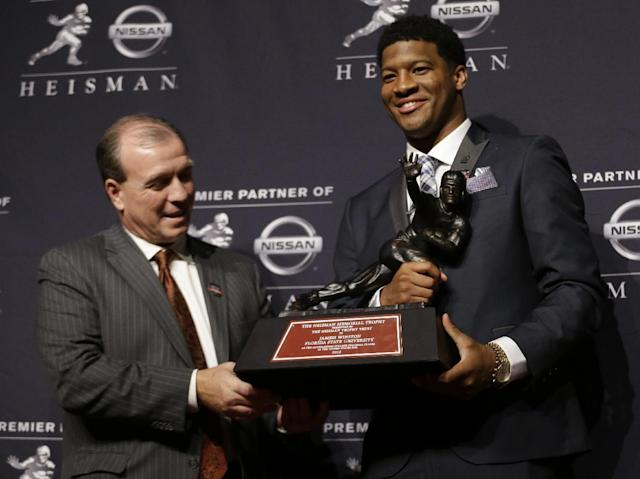 Florida State quarterback Jameis Winston, right, stands with FSU coach Jimbo Fisher while holding the Heisman Trophy after winning the award on Saturday, Dec. 14, 2013, in New York. (AP Photo/Julio Cortez)