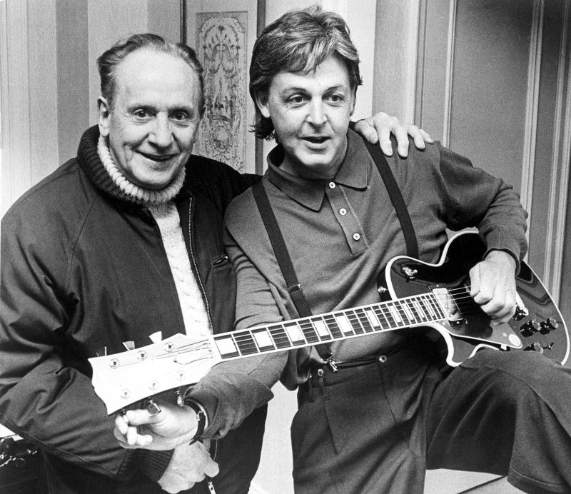 "FILE - In this May 3, 1988 file photo, Paul McCartney, right, tries out a custom-made left handed ""Les Paul Lite"" guitar presented to him by designer, Les Paul, left, in New York. Les Paul was a renown musician also known for his innovations on the solid body electric guitar and multitrack recording. The man who helped pave the way for rock 'n' roll is finally getting a permanent exhibit on June 9, 2013 at the Waukesha County Museum in his Wisconsin hometown. (AP Photo, file)"