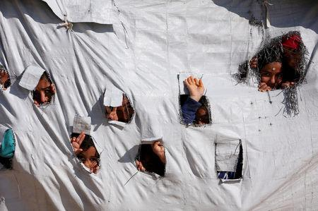FILE PHOTO: Children look through holes in a tent at al-Hol displacement camp in Hasaka governorate, Syria April 2, 2019. Picture taken April 2, 2019. REUTERS/Ali Hashisho/File Photo