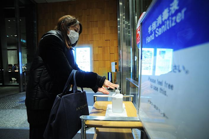 A woman wearing mask uses a hand disinfectant as measures at a shopping mall on February 11, 2020, in Tokyo, Japan.