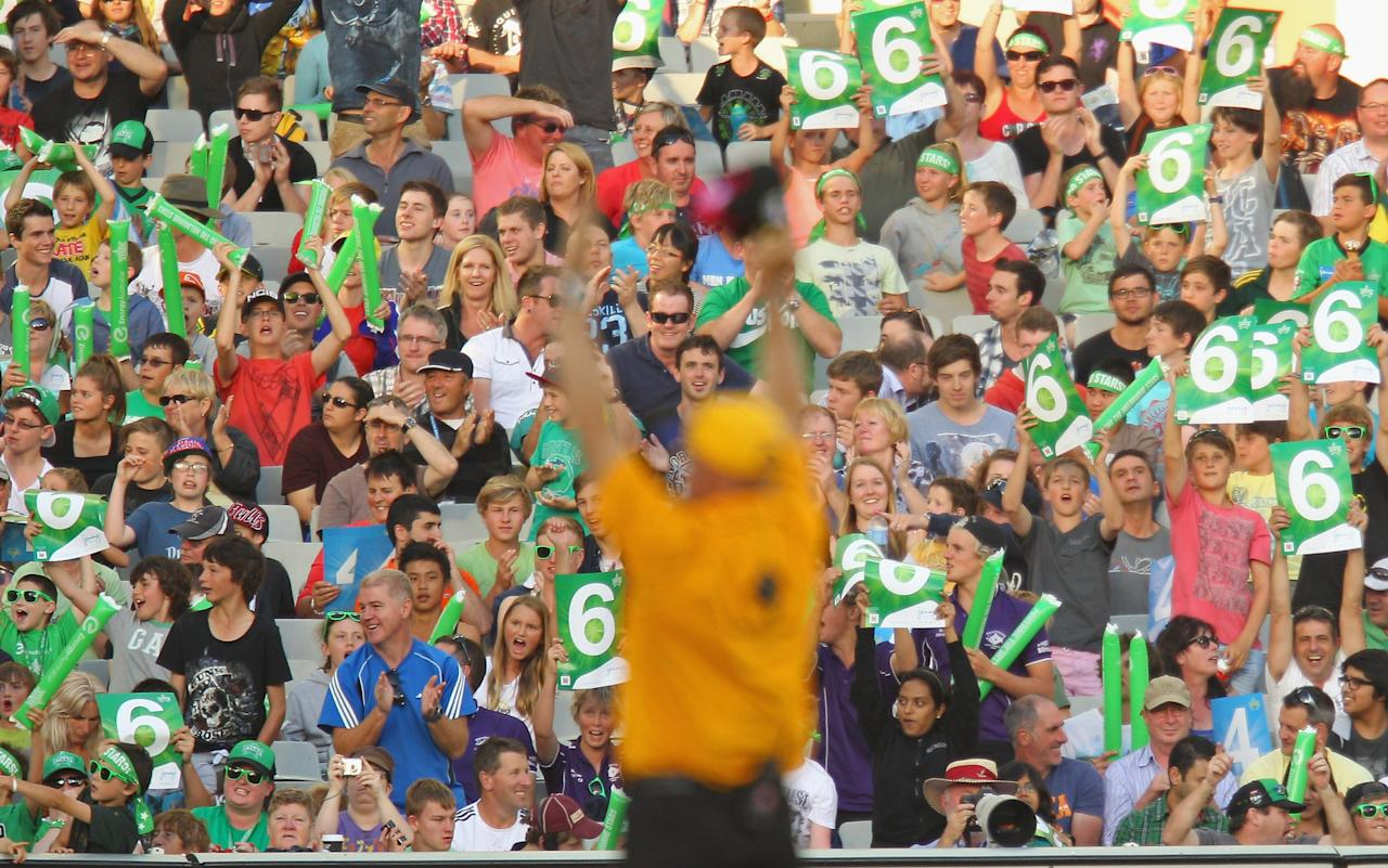 MELBOURNE, AUSTRALIA - DECEMBER 21:  The crowd cheers as the umpire signals after a six was hit by the Stars during the Big Bash League match between the Melbourne Stars and the Sydney Sixers at Melbourne Cricket Ground on December 21, 2012 in Melbourne, Australia.  (Photo by Scott Barbour/Getty Images)