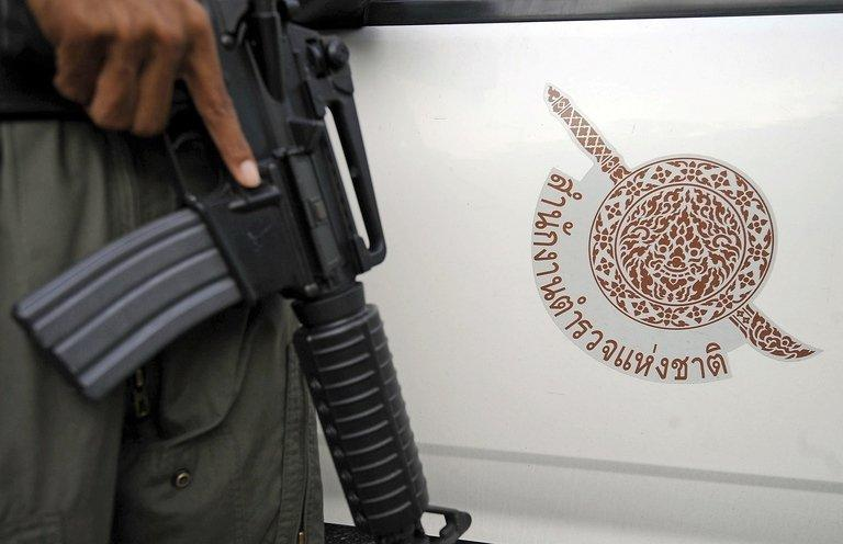 A police officer is pictured next to a police car in Thailand on March 14, 2012