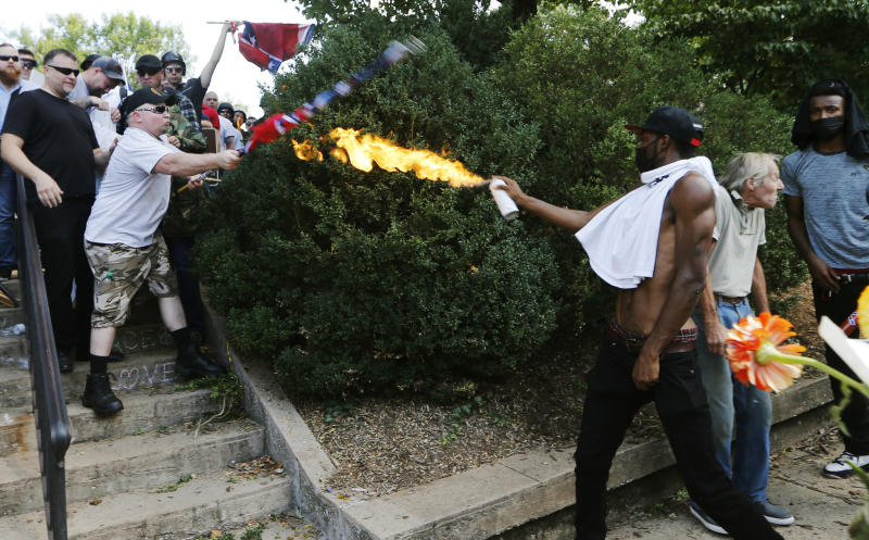 A counter demonstrator uses a lighted spray can against a white nationalist demonstrator at the entrance to Lee Park in Charlottesville, Va., Saturday, Aug. 12, 2017. Gov. Terry McAuliffe declared a state of emergency and police dressed in riot gear ordered people to disperse after chaotic violent clashes between white nationalists and counter protestors. (AP Photo/Steve Helber)