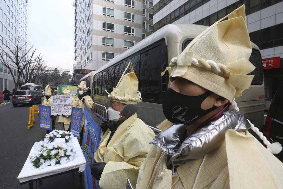 Members of an association of billiard room owners wearing traditional funeral clothes stage a rally demanding the government to allow the reopening of their businesses amid tightened social distancing rules against the pandemic in front of the ruling Democratic Party headquarters in Seoul, South Korea, Tuesday, Jan. 12, 2021. South Korean President Moon Jae-in on Monday said the government will offer COVID-19 vaccinations to everyone free of charge in phased steps. (AP Photo/Ahn Young-joon)