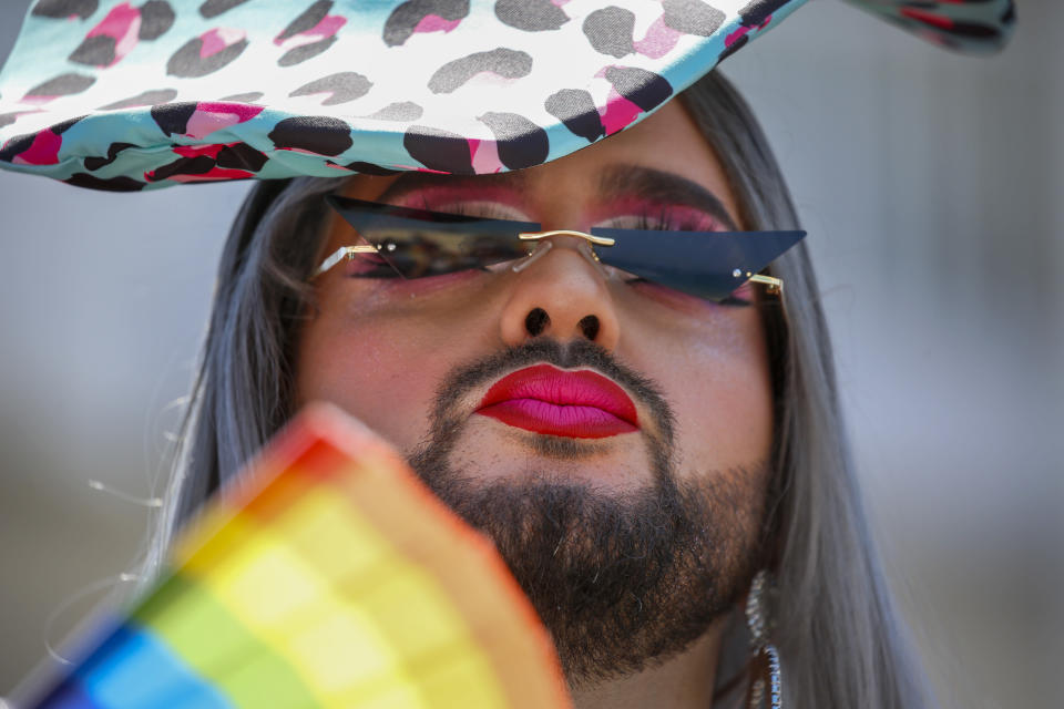 A participant pauses in the annual Pride Parade, in Tel Aviv, Israel, Friday, June 25, 2021. Thousands of people attended the parade Friday in one of the largest public gatherings held in Israel since the onset of the coronavirus pandemic. (AP Photo/Ariel Schalit)