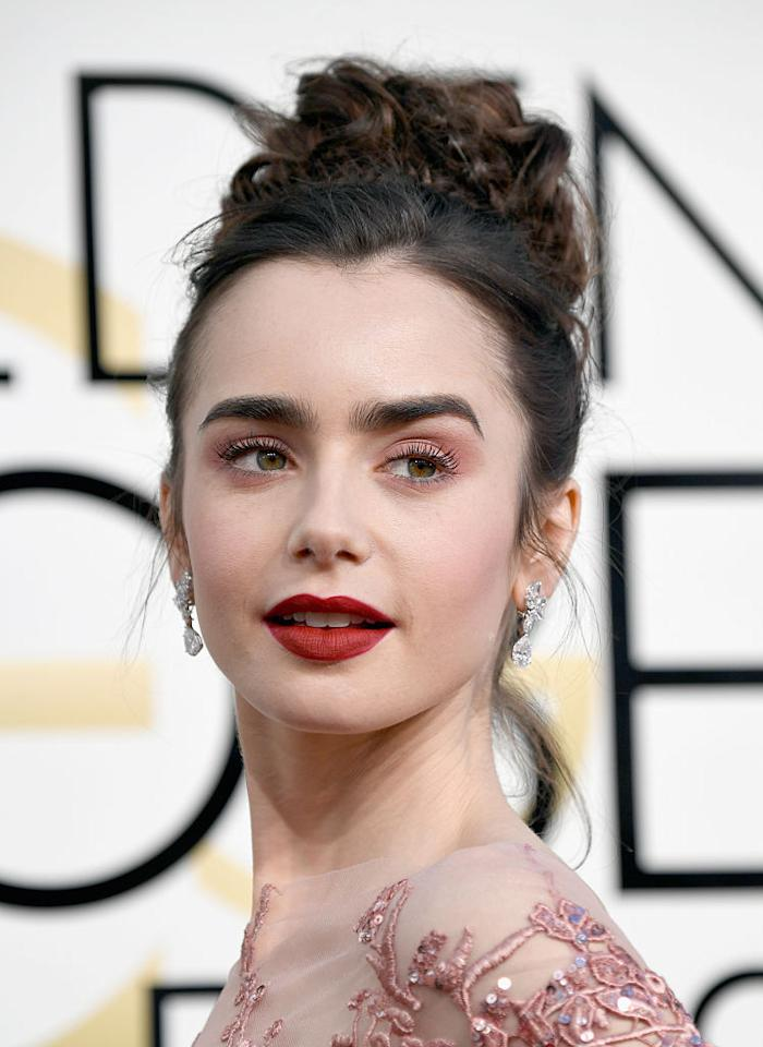 <p>Lily Collins wears a wine-stained matte lip color along with pretty pink eyeshadow. (Photo: Getty Images) </p>