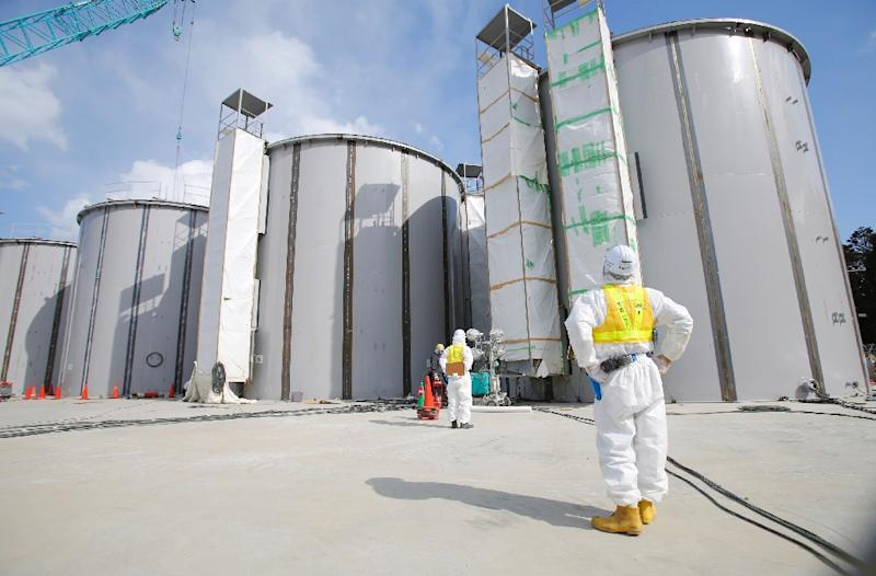 Workers in protective suits look at welding storage tanks for radioactive water, under construction in the J1 area at the Tokyo Electric Power Co's (TEPCO) tsunami-crippled Fukushima Daiichi nuclear power plant, on March 10, 2014 (AFP Photo/Toru Hanai)