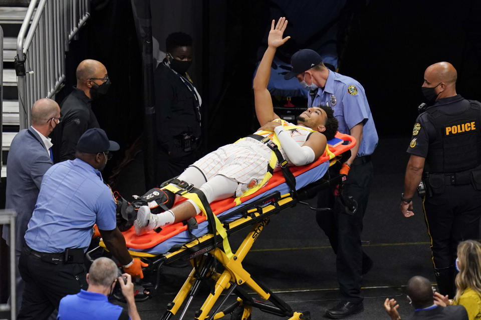 Orlando Magic guard Devin Cannady, center, waves to fans as he is taken off the court after he was injured during the first half of an NBA basketball game against the Indiana Pacers, Sunday, April 25, 2021, in Orlando, Fla. (AP Photo/John Raoux)