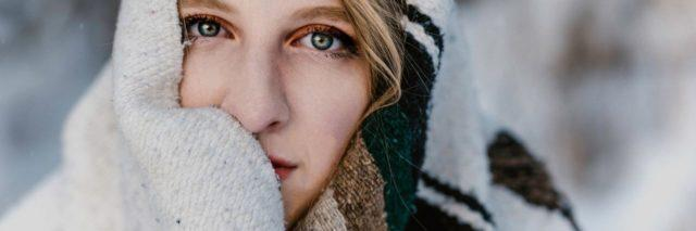 Woman wrapped in blanket looking into camera