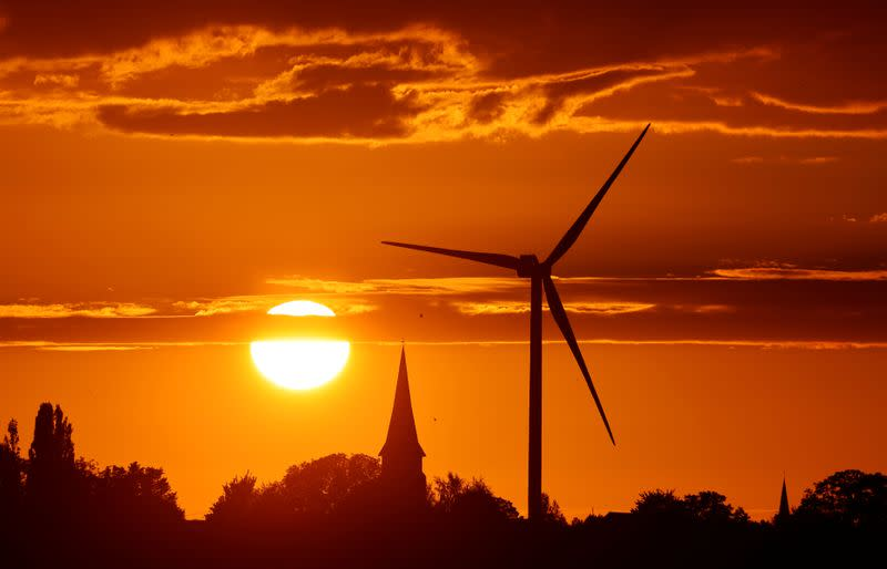 FILE PHOTO: A power-generating windmill turbine and the church of the village are pictured during sunset at a wind park in Ecoust-Saint-Mein