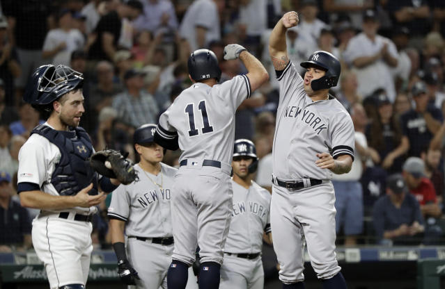 New York Yankees' Gary Sanchez, right, leaps to congratulate Brett Gardner (11) on Gardner's three-run home run, next to Seattle Mariners catcher Tom Murphy during the third inning of a baseball game Tuesday, Aug. 27, 2019, in Seattle. (AP Photo/Elaine Thompson)