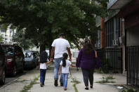 """The Baijnath family, from left, Avani, 6, Sudjendra, Nisha, 5, and Deviyan, leave St. Francis Xavier School in Newark, on Thursday, Aug. 6, 2020, after meeting with dozens of other concerned parents and students to discuss the school's permanent closure. """"They're taking so much away from these kids,"""" Sudjendra Baijnath said. """"They really enjoyed the teachers here."""" (AP Photo/Jessie Wardarski)"""