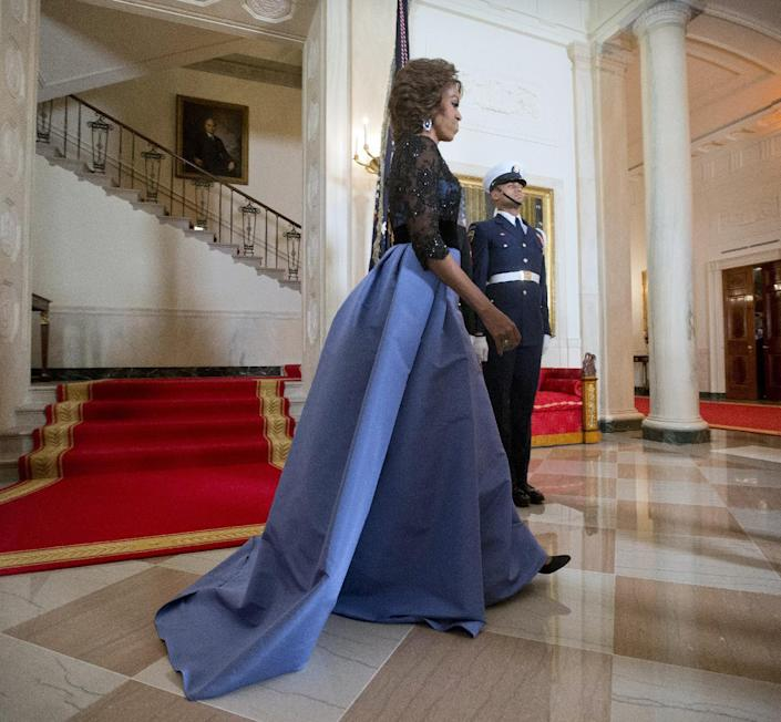 First Lady Michelle Obama walks away from the Grand Staircase after posing for the official photo with President Barack Obama with French President Francois Hollande as they arrive for a State Dinner at the White House in Washington, Tuesday, Feb. 11, 2014. (AP Photo/Pablo Martinez Monsivais)