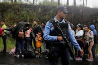 Honduran migrants queue to show their identification to the officials near to the Agua Caliente border, hoping to cross into Guatemala and join a caravan trying to reach the U.S, in the municipality of Ocotepeque, Honduras October 17, 2018. REUTERS/Jorge Cabrera