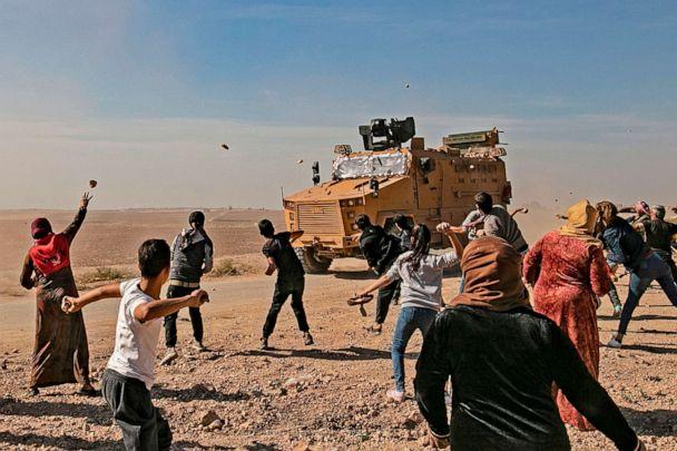PHOTO: Syrians throw stones towards Turkish military vehicles during a Turkish-Russian army patrol near the town of Darbasiyah in Syria's northeastern Hasakeh province along the Syria-Turkey border on Nov. 11, 2019. (Delil Souleiman/AFP via Getty Images)