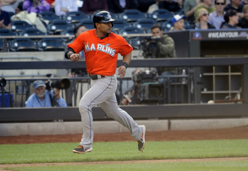 Miami Marlins' Donovan Solano runs to score on Logan Morrison's RBI-single hit off New York Mets starting pitcher Carlos Torres in the fourth inning of Game 1 of a doubleheader baseball game at Citi Field, Saturday, Sept. 14, 2013, in New York. (AP Photo/Kathy Kmonicek)