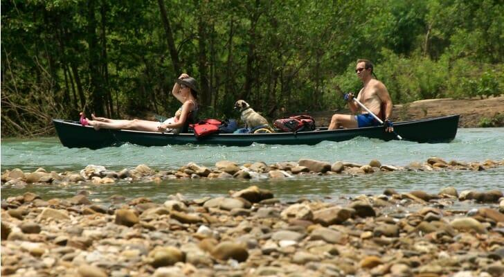 A couple with their dog in a canoe floating down an Arkansas river.