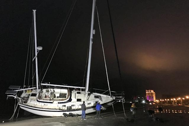 <p>A sailboat is washed up on the beach in Biloxi, Miss., early Sunday, Oct. 8, 2017, after Hurricane Nate came ashore on the Mississippi Gulf Coast. Hurricane Nate brought flooding and power outages to the Gulf Coast as it sloshed ashore outside Biloxi early Sunday, the first hurricane to make landfall in Mississippi since Hurricane Katrina in 2005. (Photo: Jeff Amy/AP) </p>
