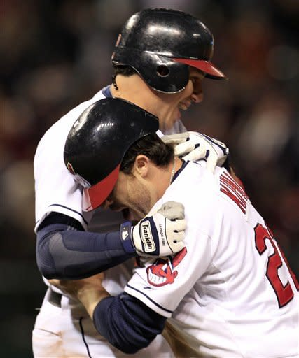 Cleveland Indians' Jason Kipnis, front, hugs Asdrubal Cabrera after Cabrera hit a game-winning RBI-single off Los Angeles Angels pitcher David Carpenter in the ninth inning of a baseball game, Friday, April 27, 2012, in Cleveland. Aaron Cunningham scored. The Indians won 3-2. (AP Photo/Tony Dejak)