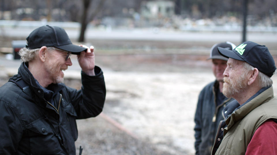 """This image released by National Geographic shows filmmaker Ron Howard, left, with Steve """"Woody"""" Culleton during the filming of the documentary """"Rebuilding Paradise"""" in Paradise, Calif. A new documentary by director Ron Howard captures a town's tough recovery following one of the most devastating wildfires in California's history.(Lincoln Else/National Geographic via AP)"""