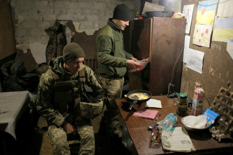 Ukrainian servicemen cook at a position on the frontline with some fearful that Ukraine goes into the summit talks in a weak position which may force Kiev to give ground