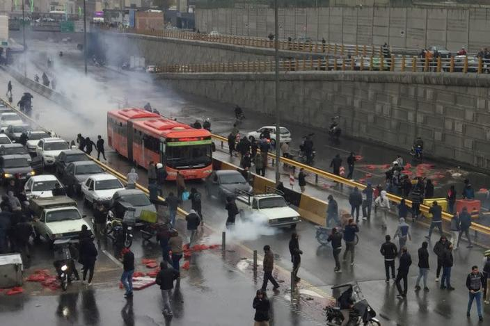 FILE PHOTO: People protest against increased gas price, on a highway in Tehran