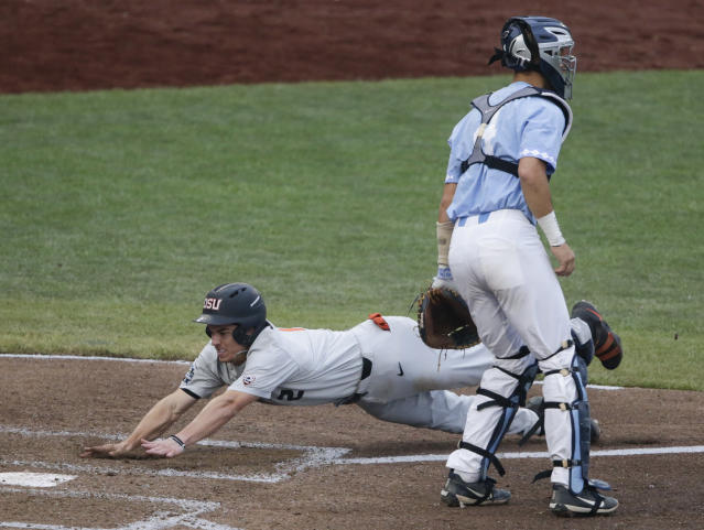 Oregon State's Cadyn Grenier slides home as North Carolina catcher Brandon Martorano (4) waits for the throw on a double by Trevor Larnach (11) in the third inning of an NCAA College World Series baseball elimination game in Omaha, Neb., Wednesday, June 20, 2018. (AP Photo/Nati Harnik)