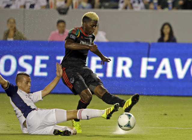 Real Salt Lake midfielder Luis Gil, left, slides against Los Angeles Galaxy midfielder Gyasi Zardes in the first half of an MLS soccer game in Carson, Calif., Saturday, Aug. 17, 2013. (AP Photo/Reed Saxon)