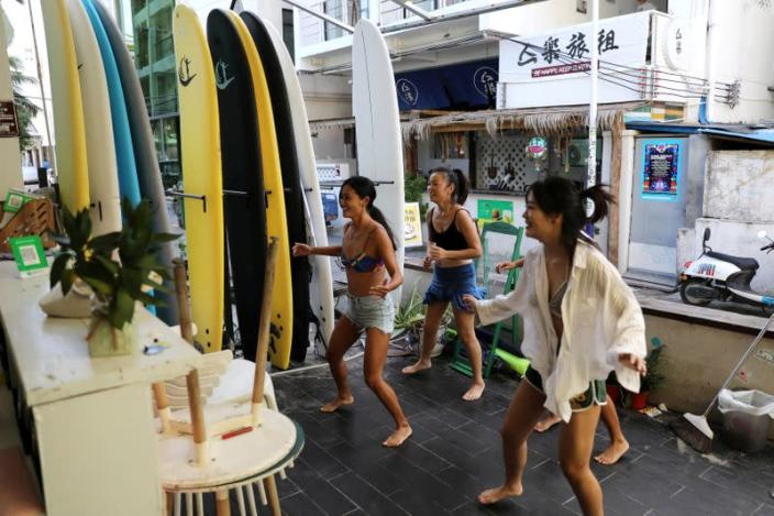 FILE PHOTO: Women exercise during an online gym class at a surfing hotel in Houhai village in Sanya