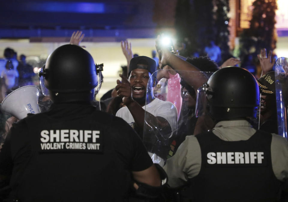 A protester confronts police officers in riot gear on Thursday night, June 24, 2021 in downtown Rock Hill, S.C. Two nights of protests outside a South Carolina police station have followed the arrest of two men seen on a Facebook video being wrestled and punched by Rock Hill officers. (Tracy Kimball/The Charlotte Observer via AP)