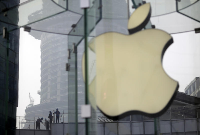 FILE - In this Friday, July 20, 2012 file photo, workers clean the rooftop of a building near an Apple Store in Shanghai, China. Apple was one of the star performers of the first quarter of 2012 and was probably the year's most talked-about company. Apple also announced a dividend and overtook Exxon Mobil as the United States' most valuable company. Investor optimism faded though and prompted a sell-off. (AP Photo/Eugene Hoshiko, File)