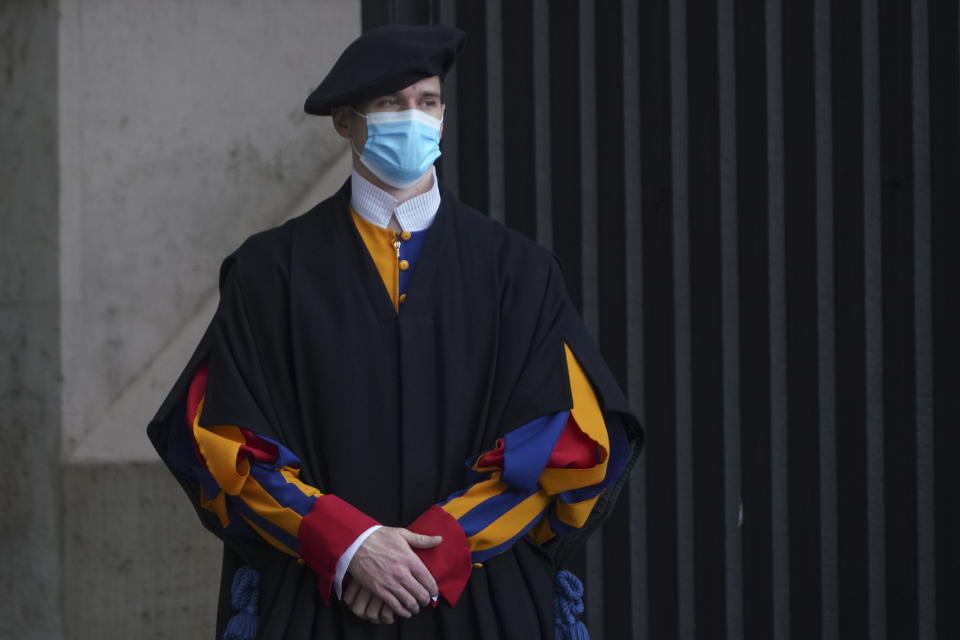 A Swiss Guard stands at the Vatican, Monday, Oct. 12, 2020. On Monday, Oct. 12, 2020, the Vatican said in a statement that four Swiss Guards have tested positive for the coronavirus, as the surge in infections in surrounding Italy enters the Vatican walls. (AP Photo/Andrew Medichini)